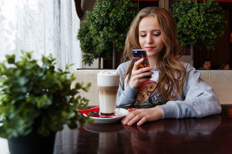 girl-using-social-media-apps-in-cafe-