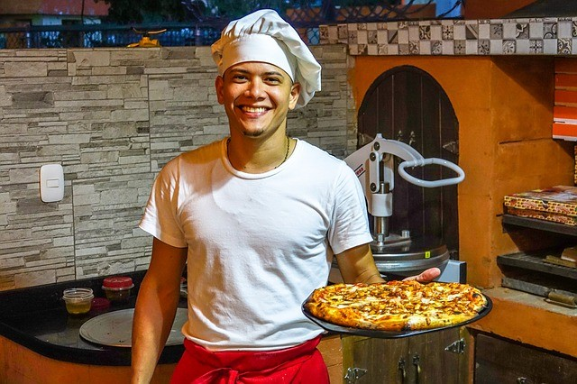 a-happy-cook-holding-pizza-ordered-via-food-delivery-app